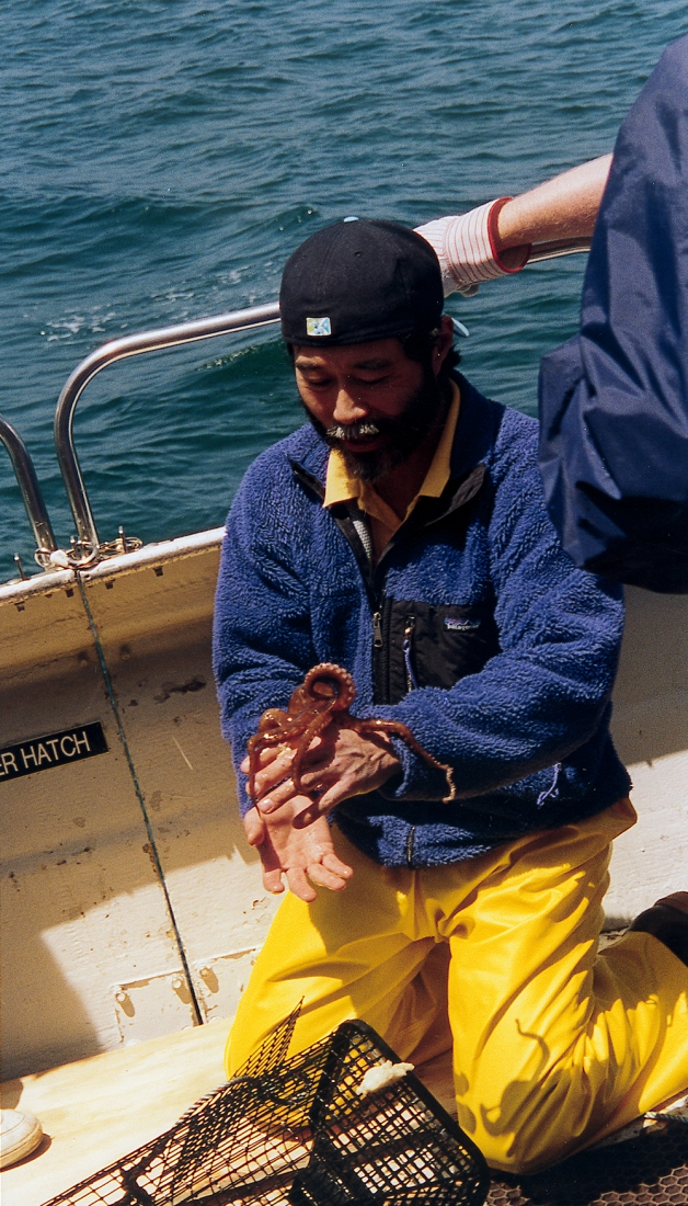 A man on a boat holding an octopus.