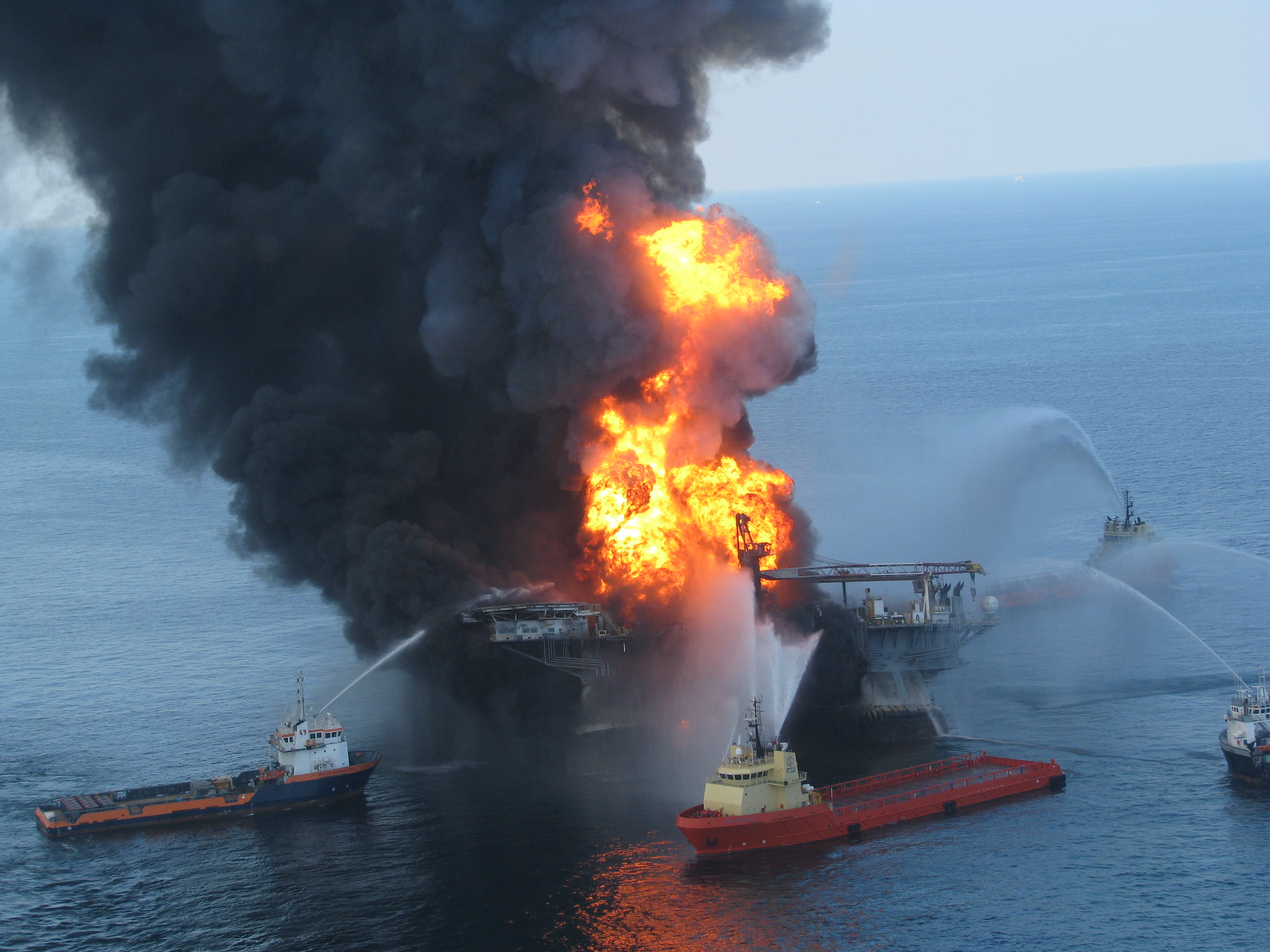An explosion on an oil rig with several boats around it.