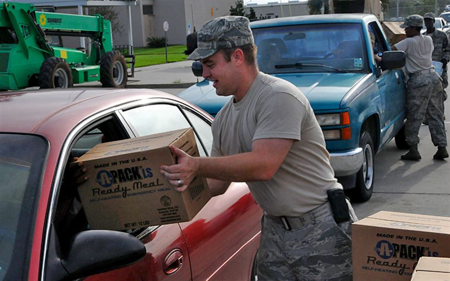 "A man in military uniform handing a box labeled ""Ready Meal"" to a person in a car."