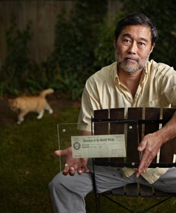 A man sitting on a chair holding a framed check with a cat in the background.