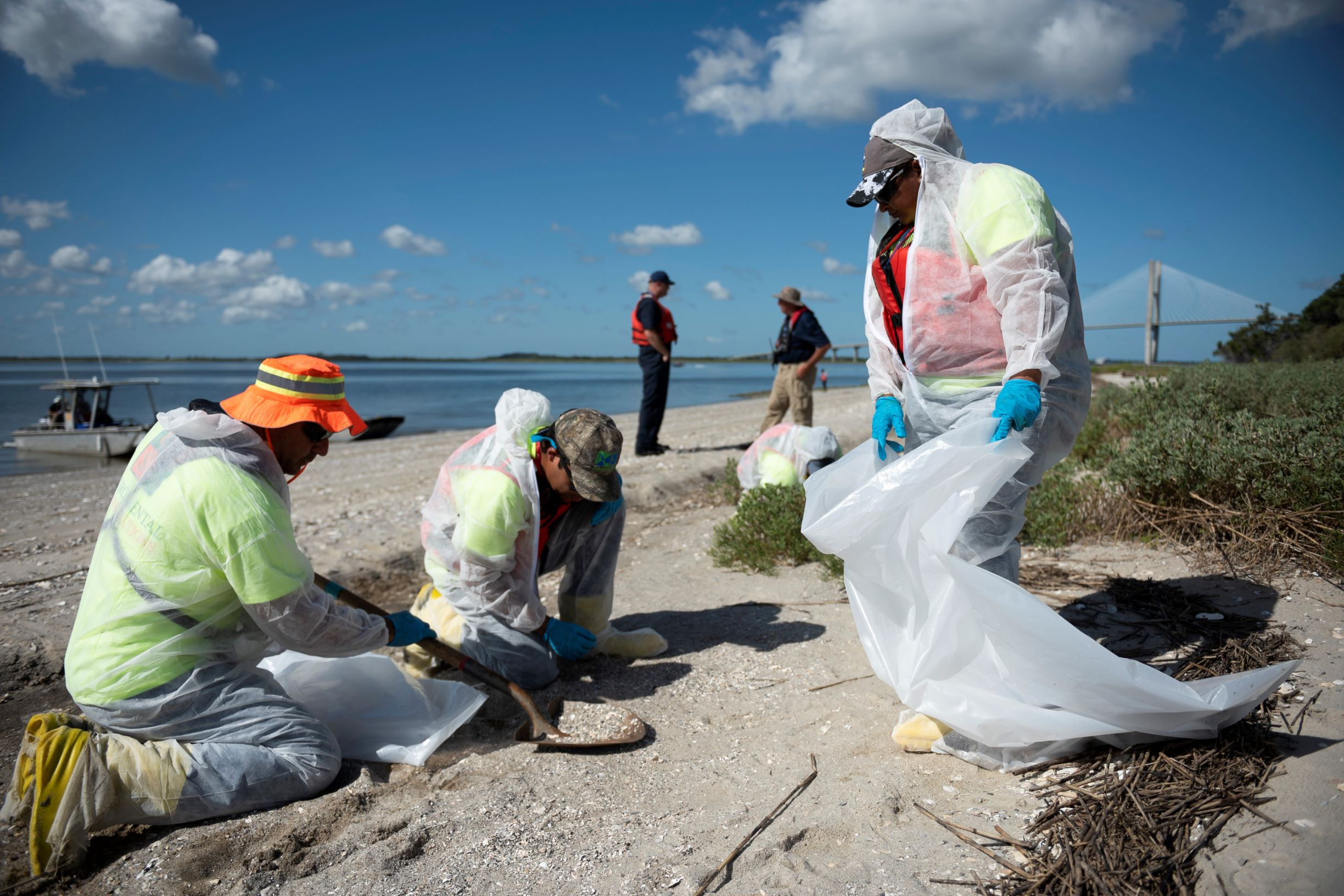 Several people in protective suits shoveling up sand from a beach into a garbage bag.
