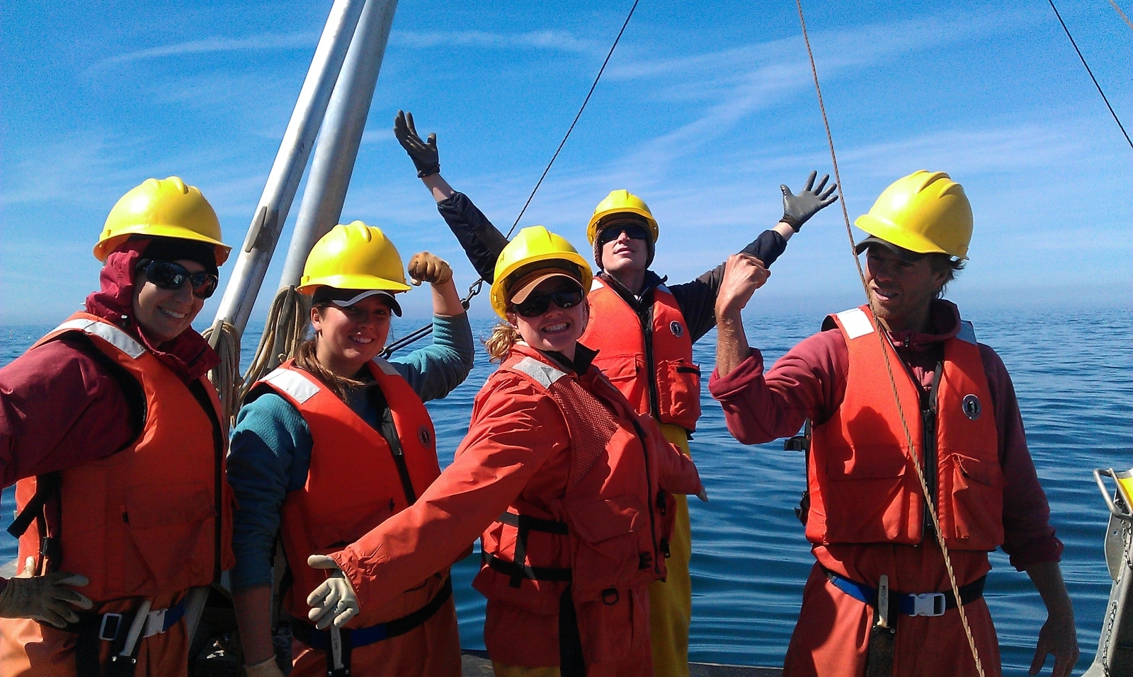 A group of people wearing hard hats and life vests on a boat.
