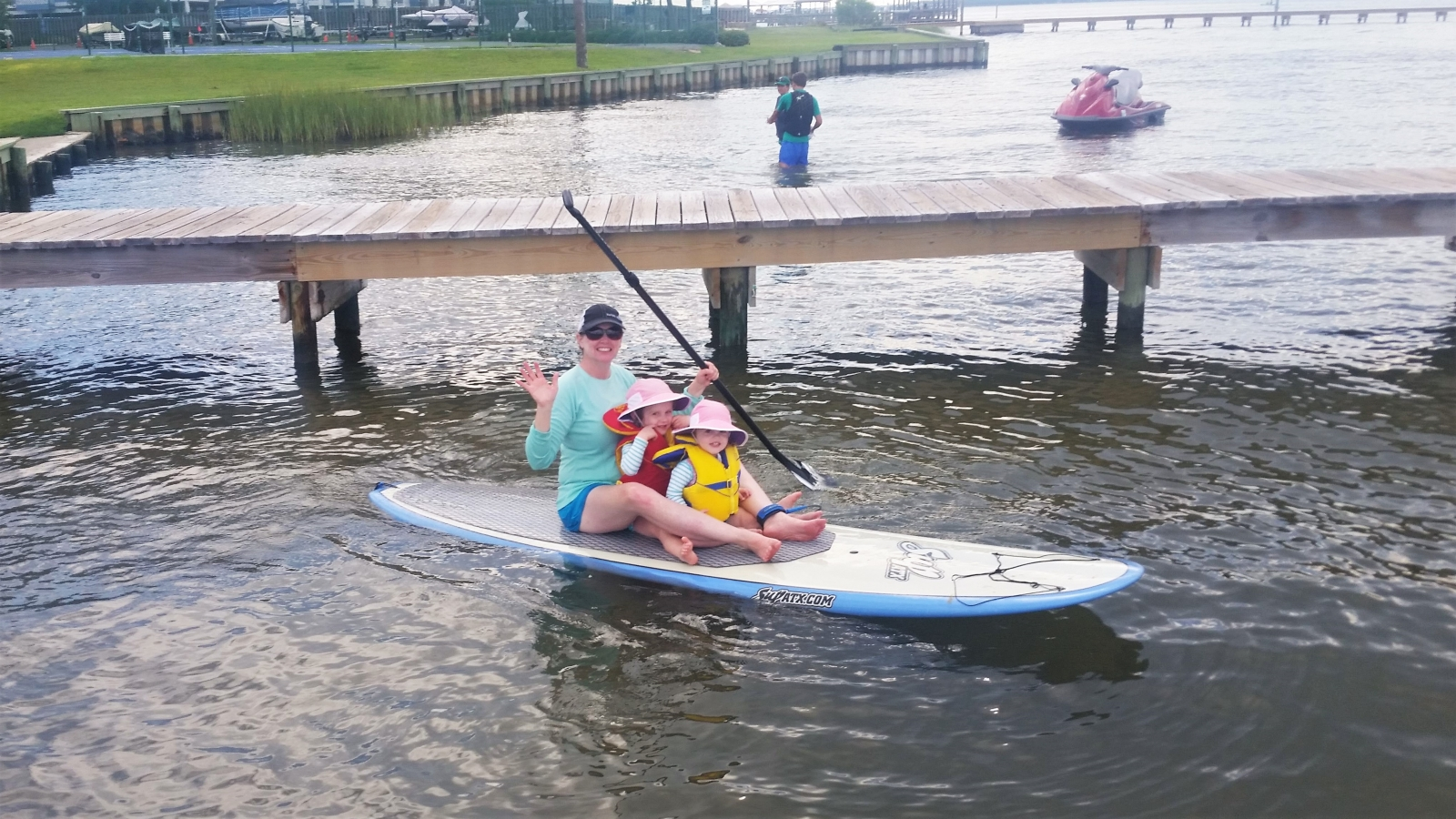 A woman and two children sitting on a paddleboard with a dock behind them.