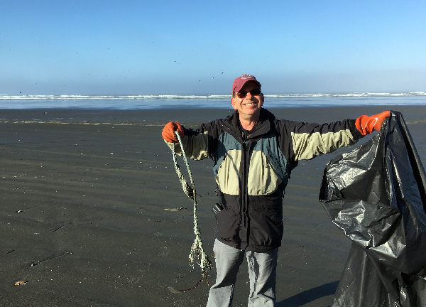 Man holding up a piece of debris on a beach.