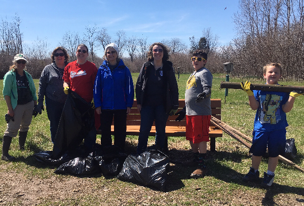Group posing with bags of debris.