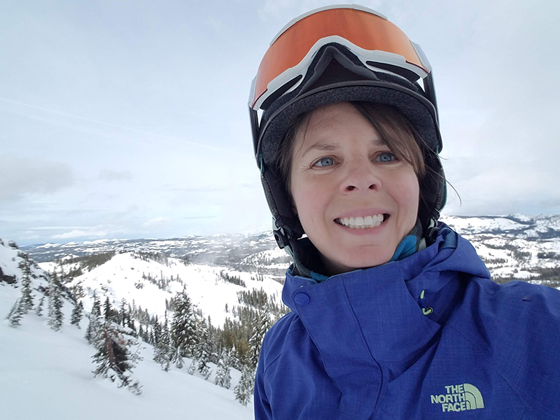 A woman in ski gear with a snowy mountain in the background.