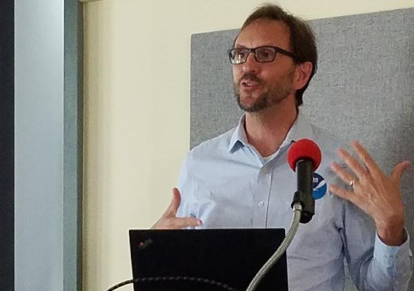 Man making a presentation at a lectern.