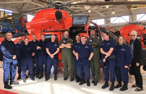 Large group poses in front of a helicopter.