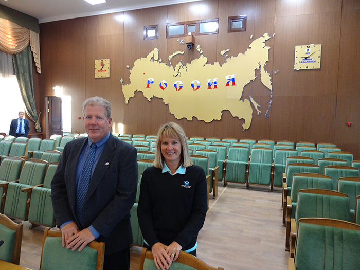 Two people posing for a photo in a meeting space.