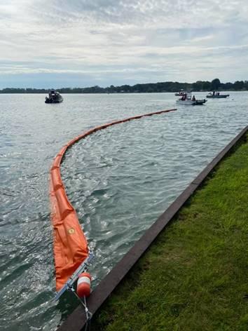 Orange boom floating on water.
