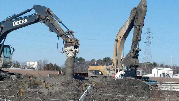 Large cranes operating in a muddy area.
