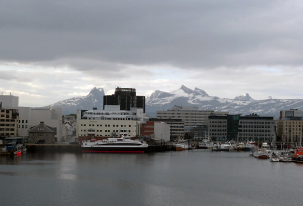 Seaport with snow-capped mountains in background.
