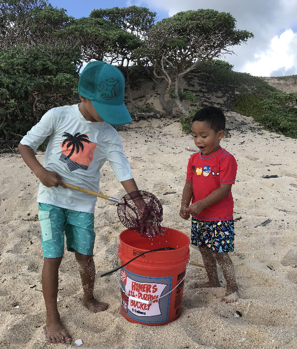 Two children putting debris into a bucket on a beach.