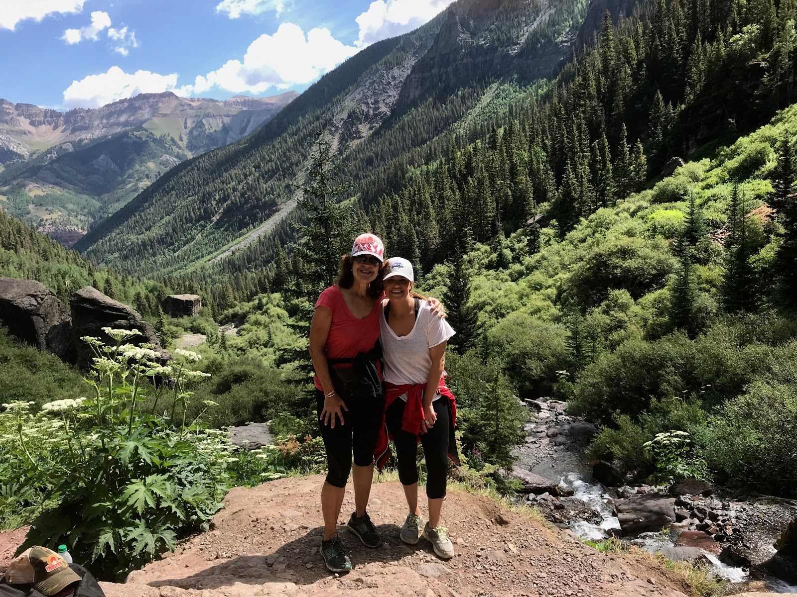 Two people pose for a photo with mountains in the background.