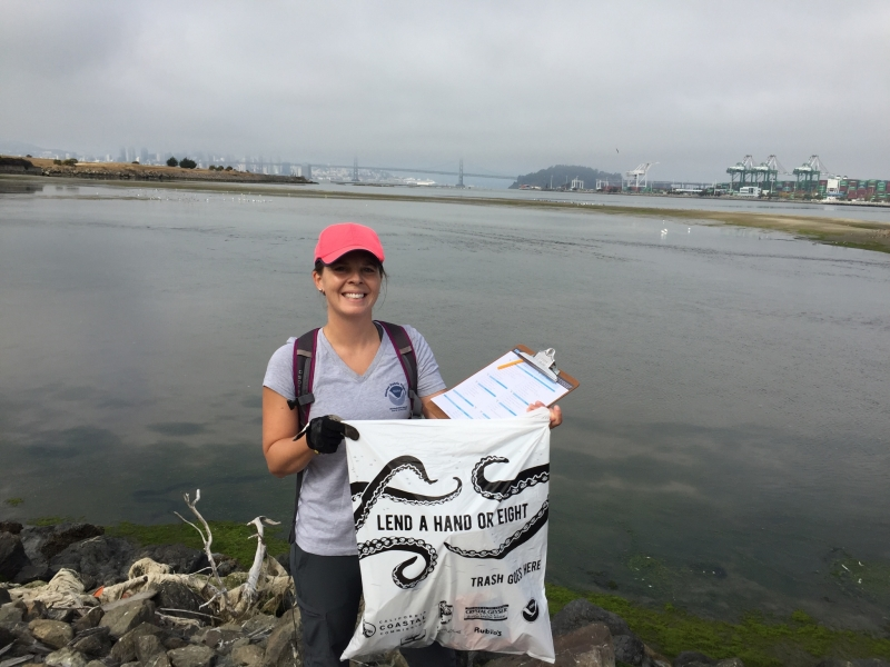 "A woman holding up a plastic bag that says ""lend a hand or eight"" with a body of water and an industrial shoreline in the background."
