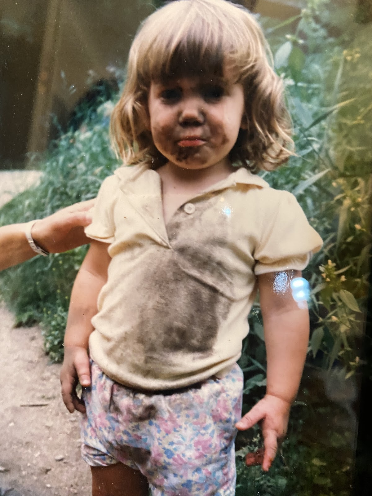 A child with mud on her face and clothes.