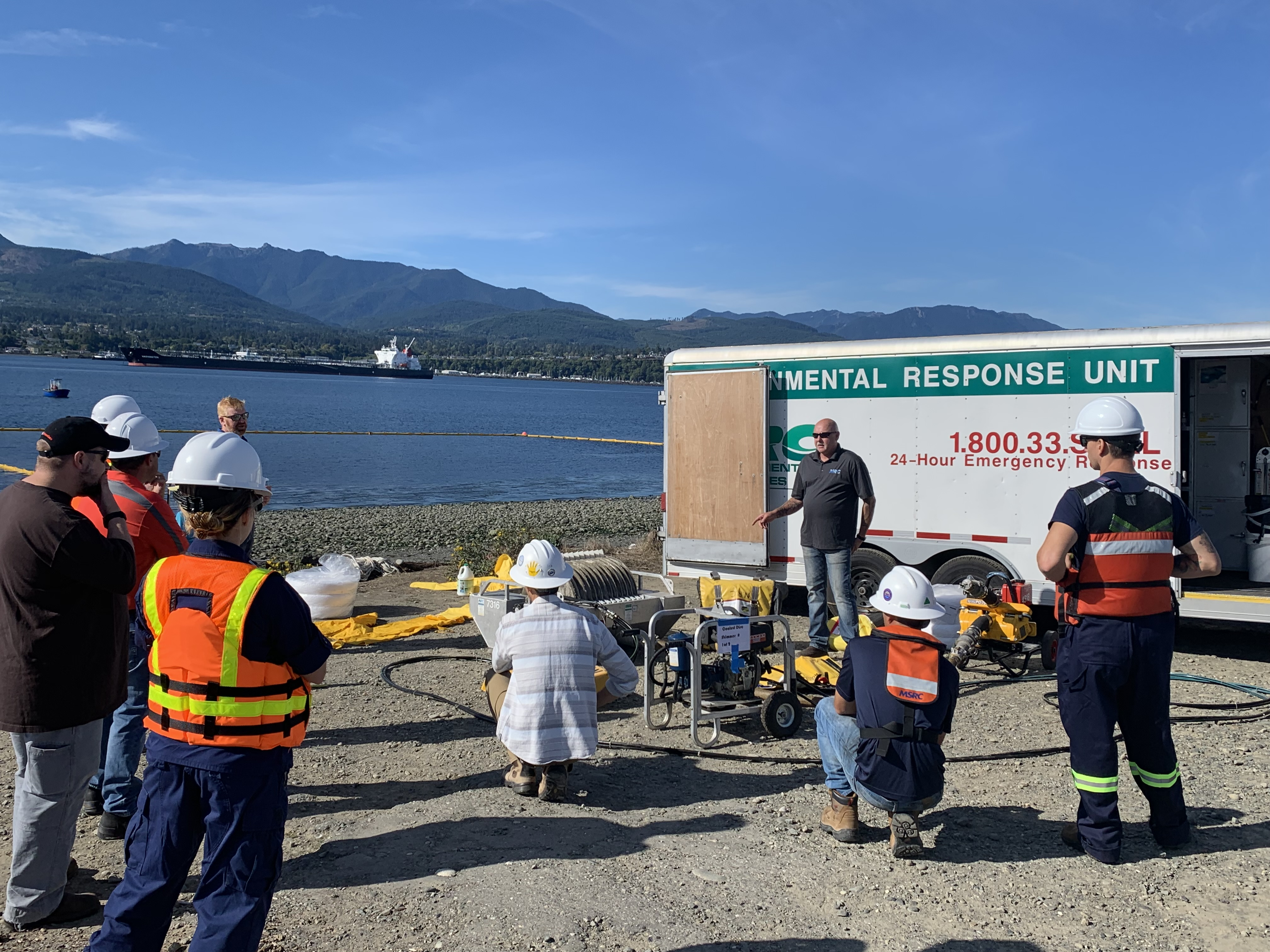 "A group of people standing in front of an ""Environmental Response Unit"" on a shoreline."