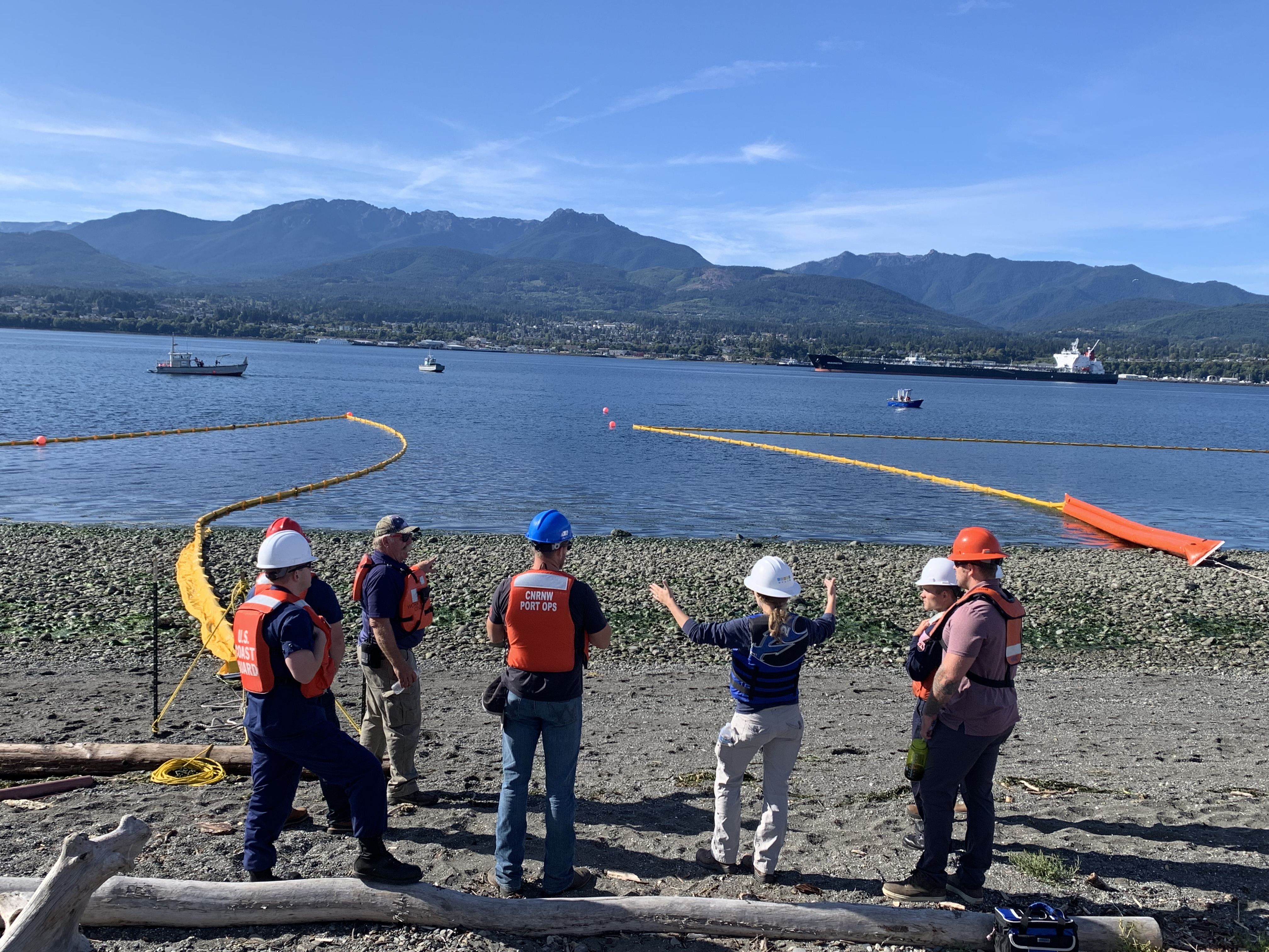 A group of people in response gear standing on a shoreline with pollution boom extending out across the water.
