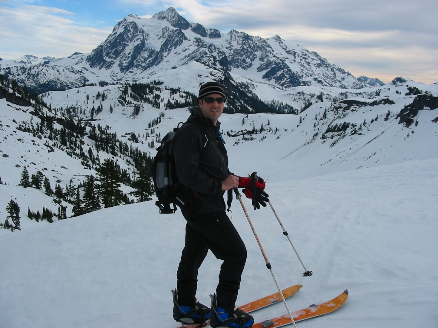A man on skis with a snow-covered mountain landscape in the background.