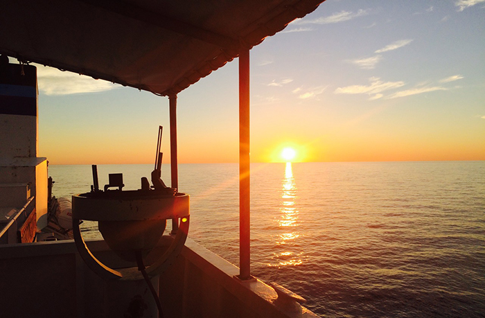 A sunrise as seen from a vessel in water.