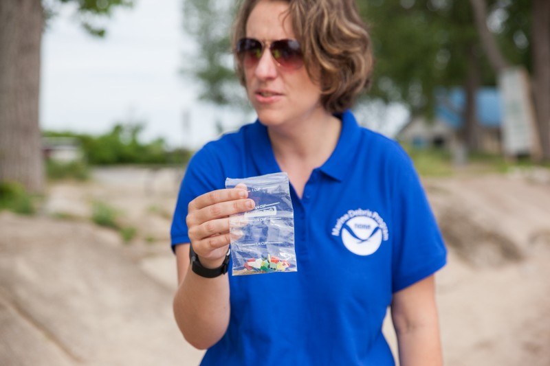 A woman holding a bag of microplastics.