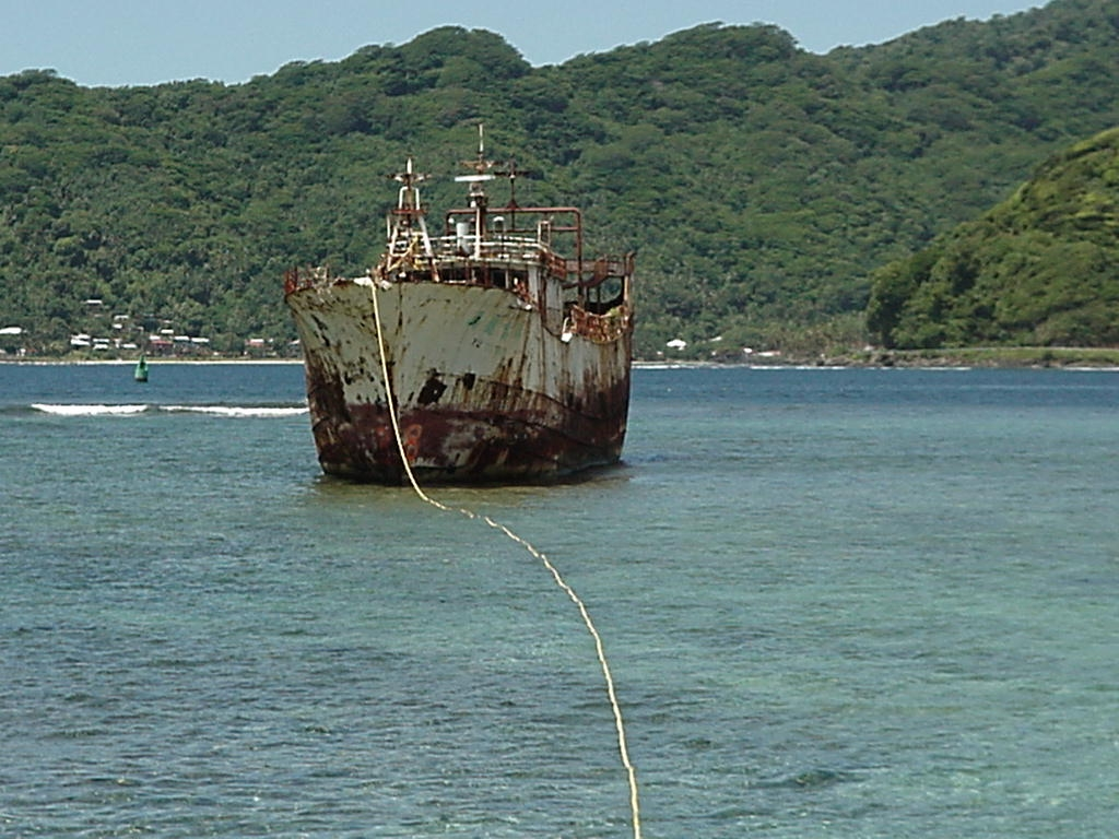 A grounded derelict vessel with a pumping line coming from it.