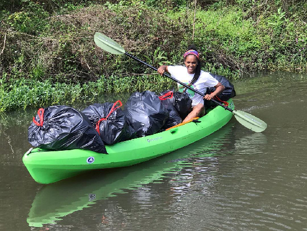 Woman paddling a kayak with bags of trash.