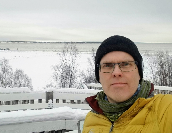 A man posing for a photo with a wintery landscape behind him.