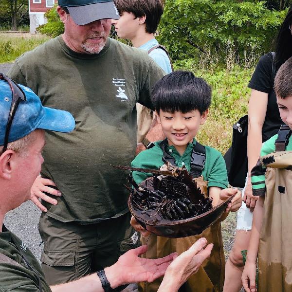Men showing children a horseshoe crab.