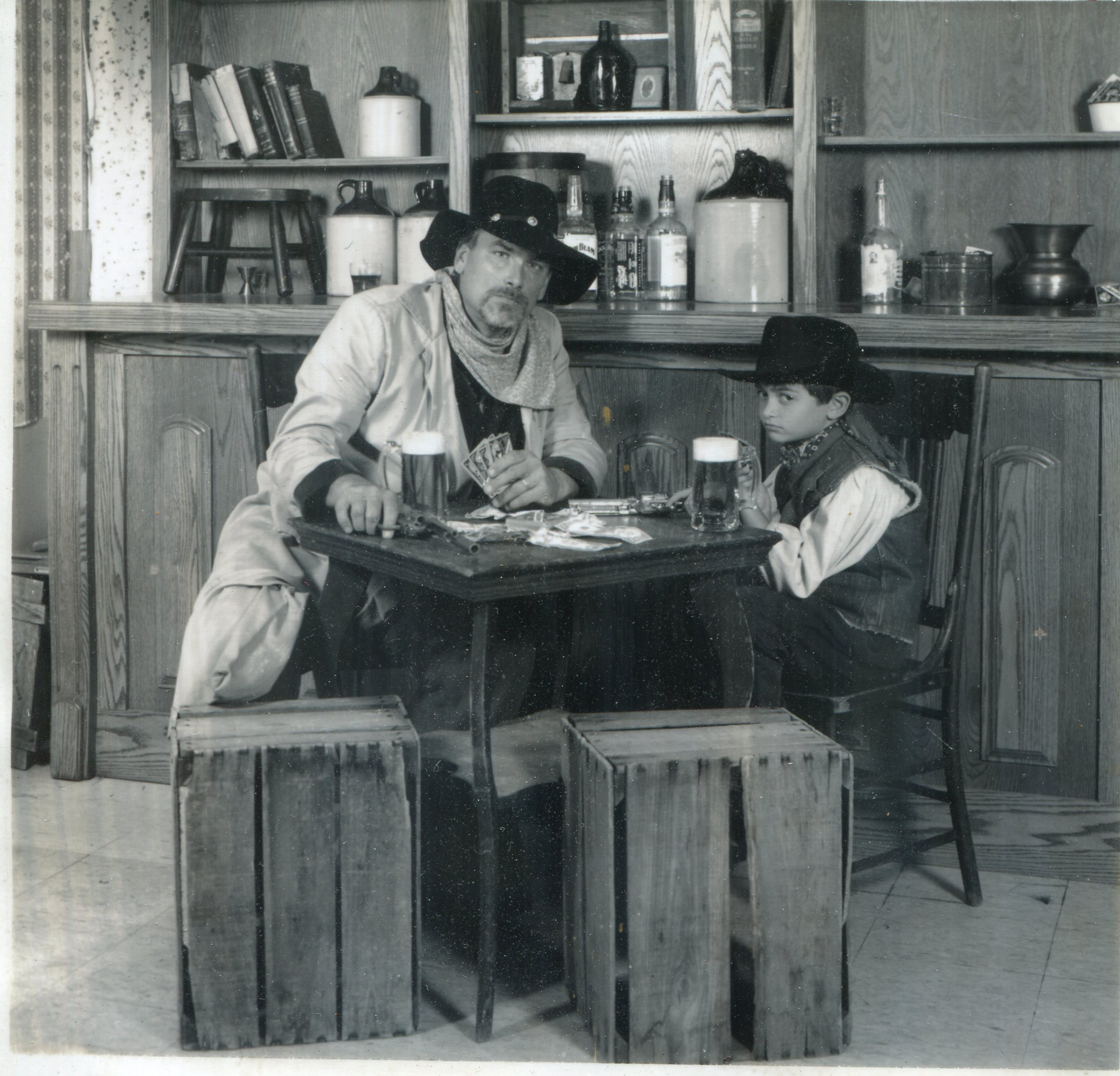 A black and white photo of a man and a child in old western clothes.