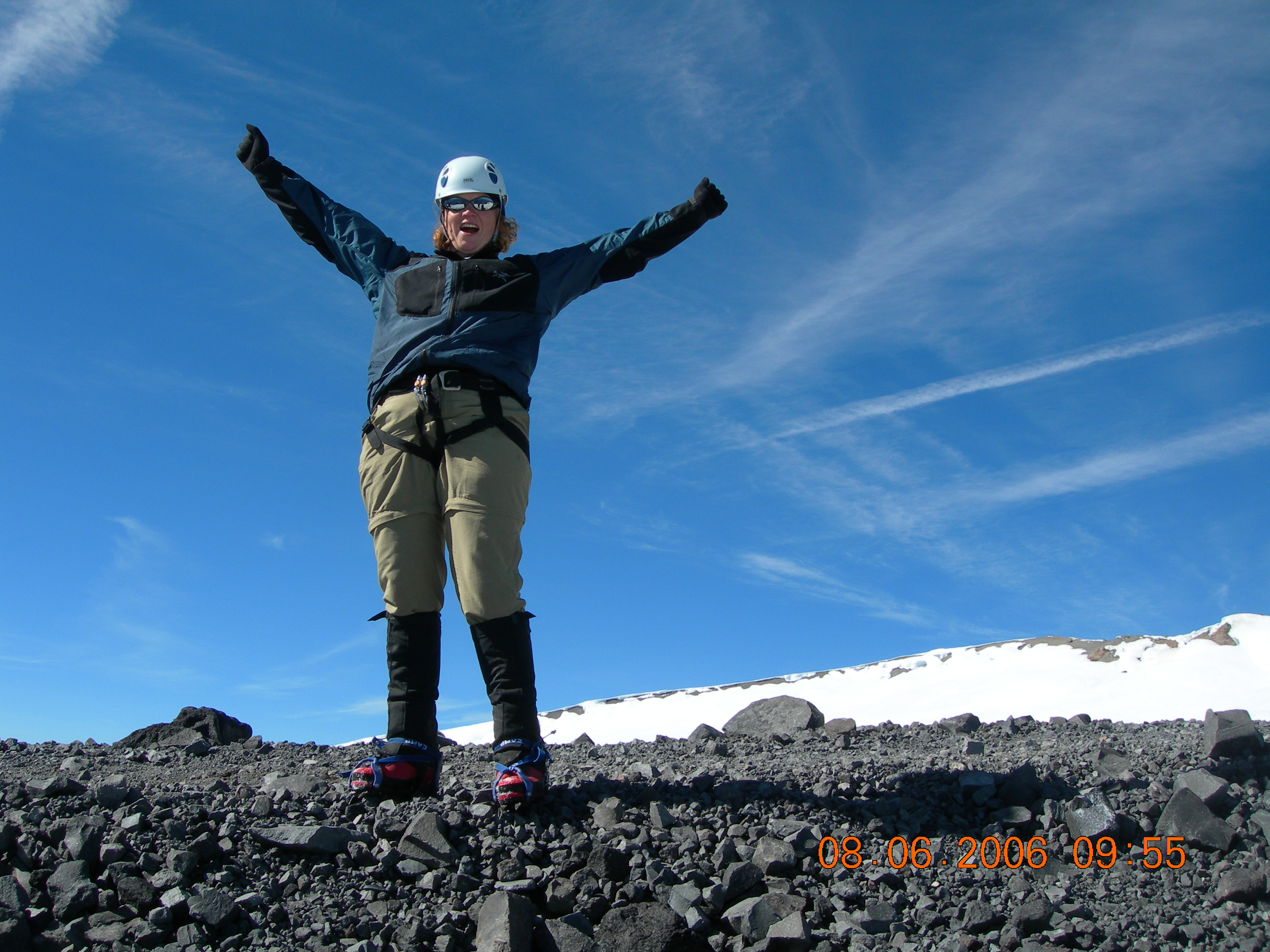 A woman standing on the top of a mountain with her arms in the air.