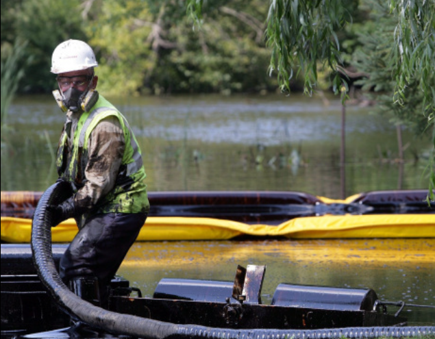 Spill responser pulls oiled boom into small boat.