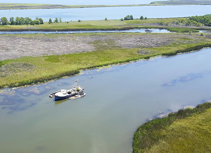 Aerial view of abandoned vessels with osprey nest on mast, located in Florida waterway.