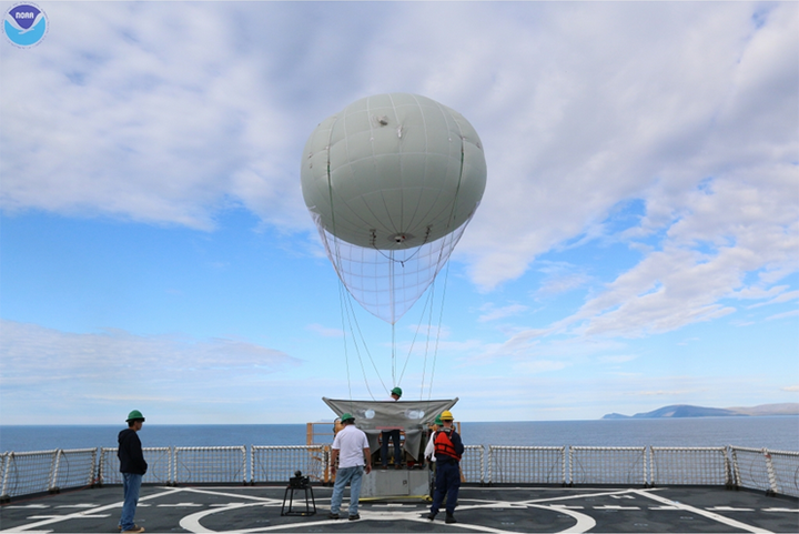 The Aerostat balloon tethered to a ship with people on deck.