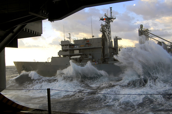 Rough seas pound the hull of support ship USNS Arctic as it sails alongside aircraft carrier USS Harry S. Truman.