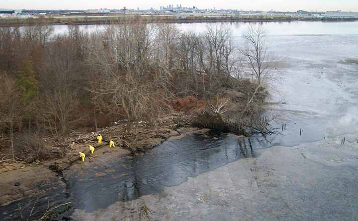 Workers clean oil from an island shoreline on the Delaware River.