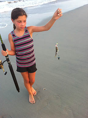 A young girl goes surf fishing with her father in the early evening. (NOAA)<br />     </div>