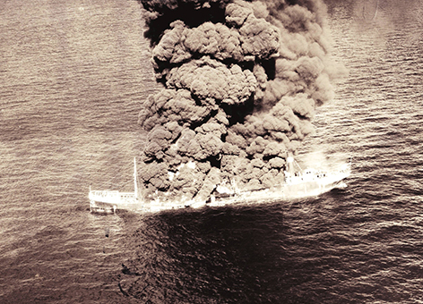 A black and white photo of smoke billowing from a sinking vessel.