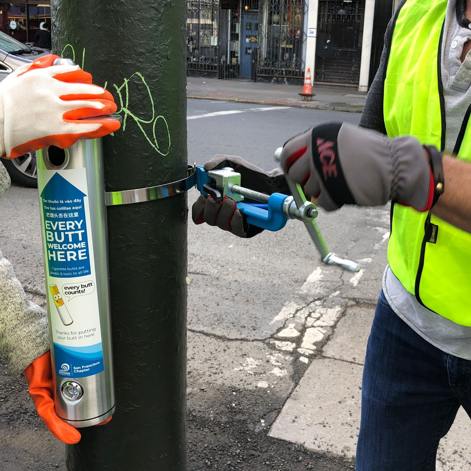 A metal cigarette butt disposal canister getting installed onto a pole along the street.