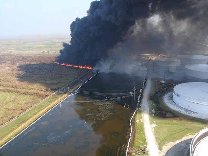 Oil being burned off of the marsh next to oil tanks.