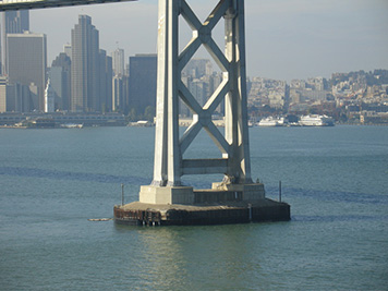 In the foreground, the Bay Bridge tower that was hit by the M/V Cosco Busan, spilling oil into San Francisco Bay and the Pacific Ocean.