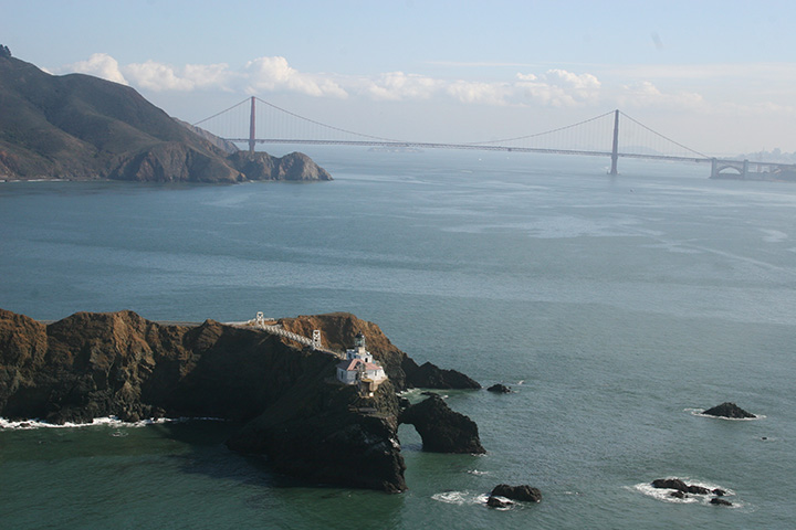 Point Bonita is in the foreground, looking across sheens of lighter colored oil from the Cosco Busan spill and eastward to Golden Gate Bridge and San Francisco Bay.