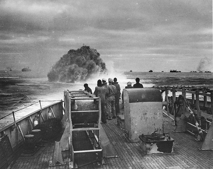 A Coast Guard ship's crew watches an explosion in the water ahead.