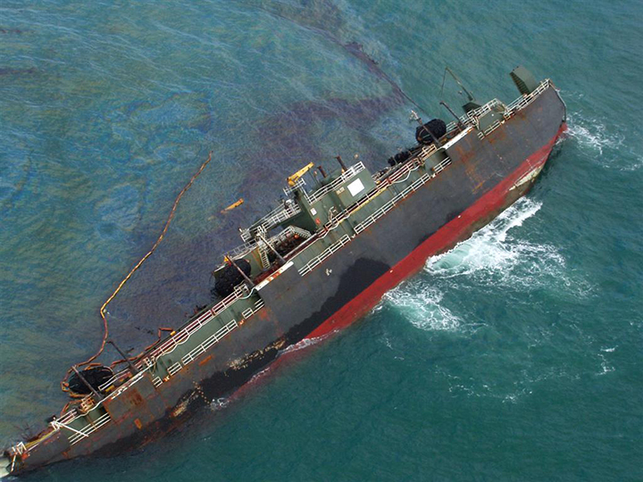 A large ship on its side, leaking dark oil on the ocean surface.