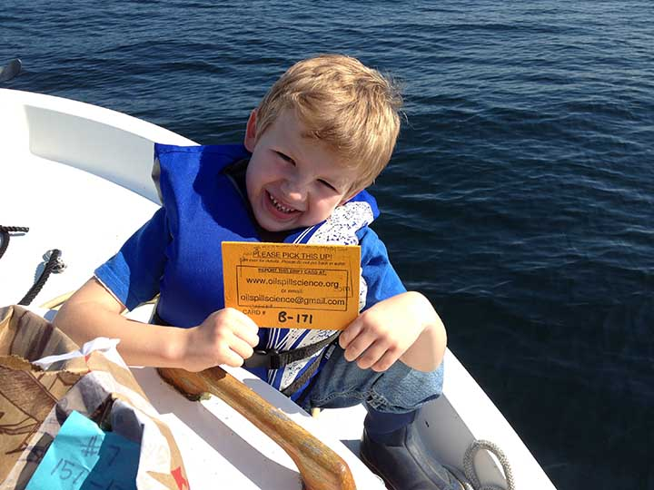 A young boy in a life jacket holding a yellow wooden card and sitting on the edge of a boat.