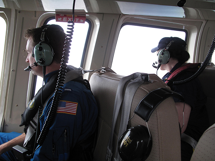 Two Coast Guard observers looking out a helicopter window.