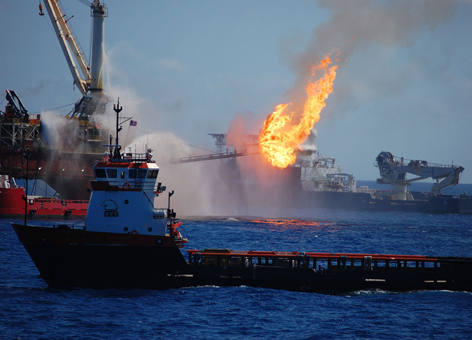 Several vessels pumping pressurized water at a fire on an oil platform.