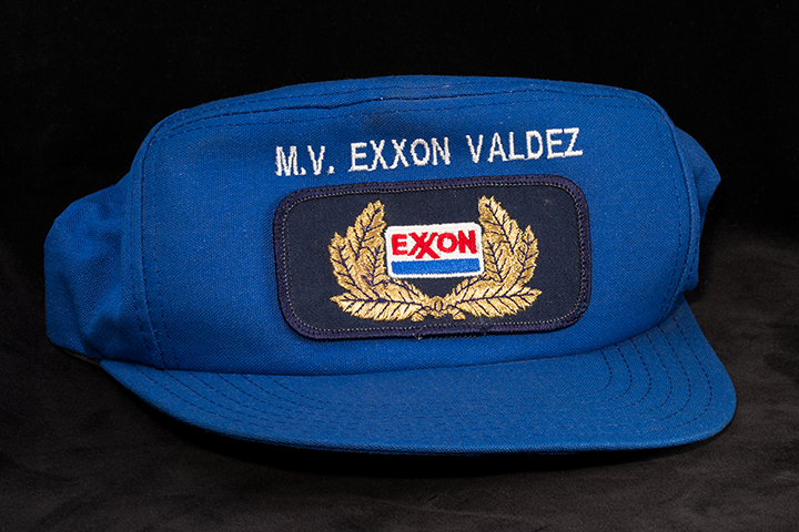 A blue baseball cap with Exxon Valdez and the Exxon Shipping Company logo.