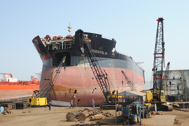 Ship being dismantled on a beach in India.
