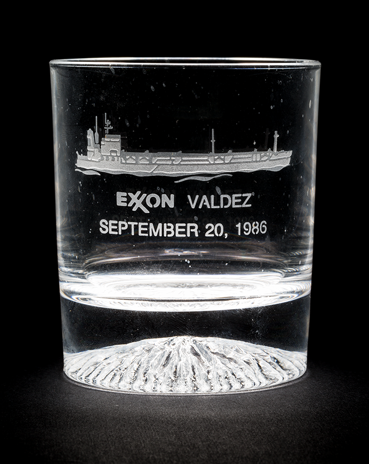A high ball glass engraved with the image and name of the tanker Exxon Valdez along with the date September 20, 1986.